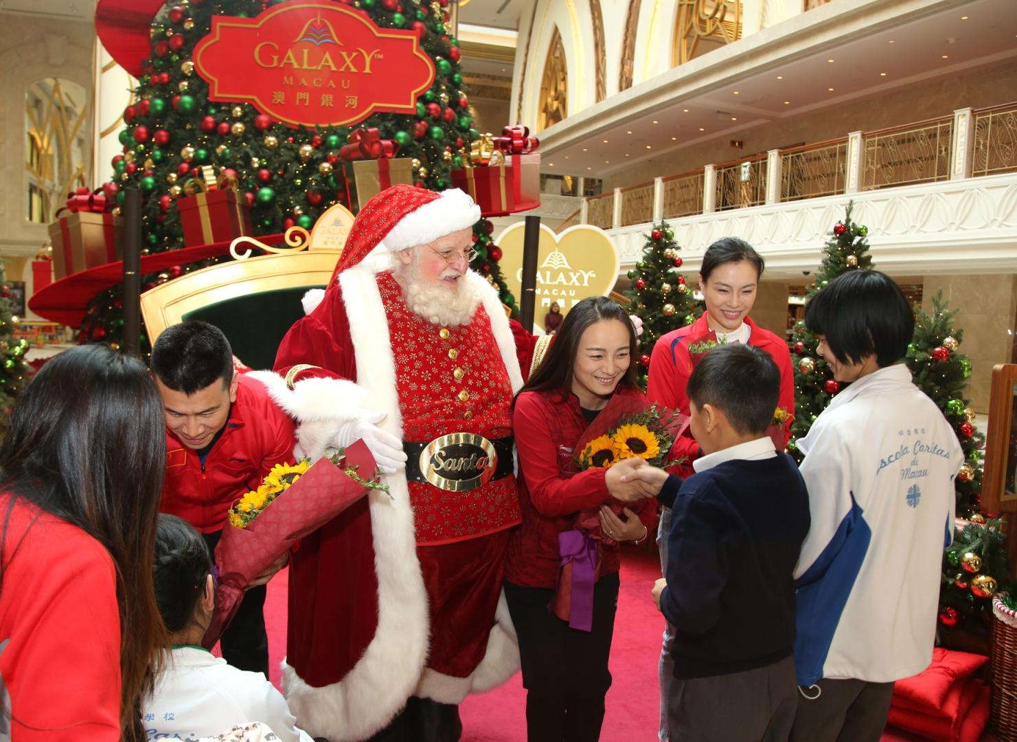 On the afternoon of December 11, the three Chinese gold medalists including Wu Minxia, Han Xiaopeng and Li Nina arrived at Santa's Grotto in Galaxy Macau's East Square, where students from Escola Caritas de Macau welcomed them with bouquets of flowers.